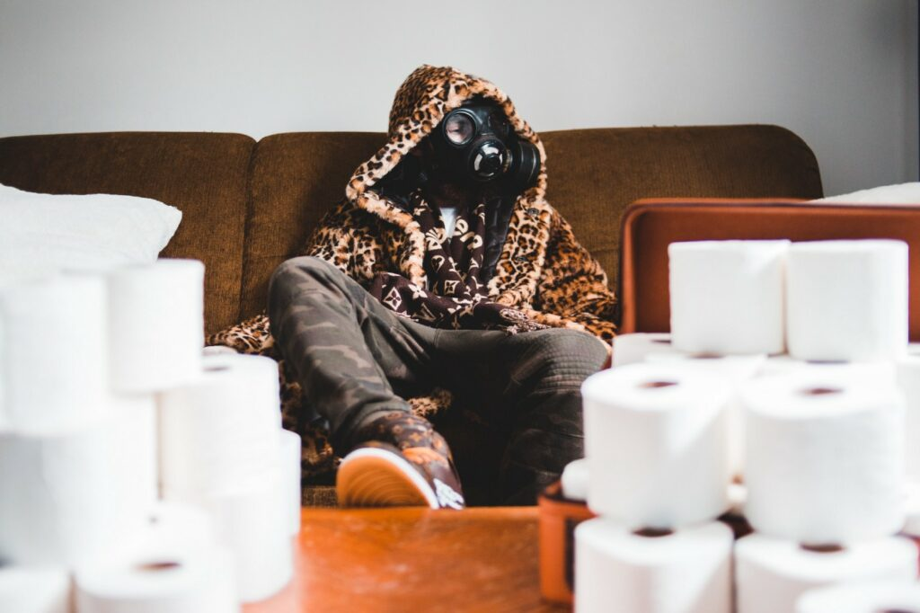 man in mask sitting with a pile of toilet rolls