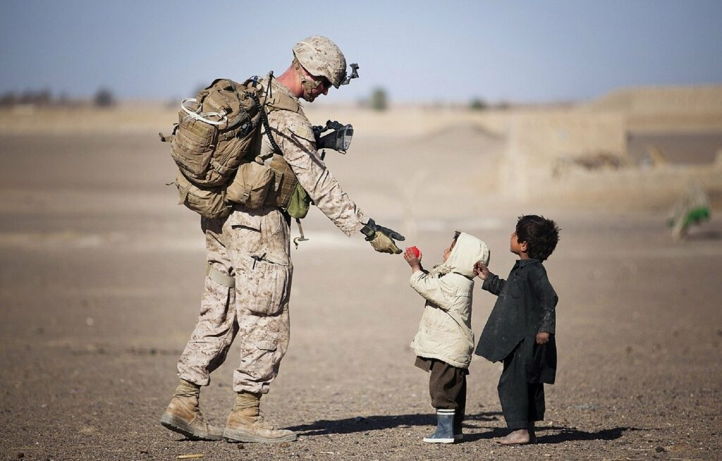 Soldier giving fruit to kids.