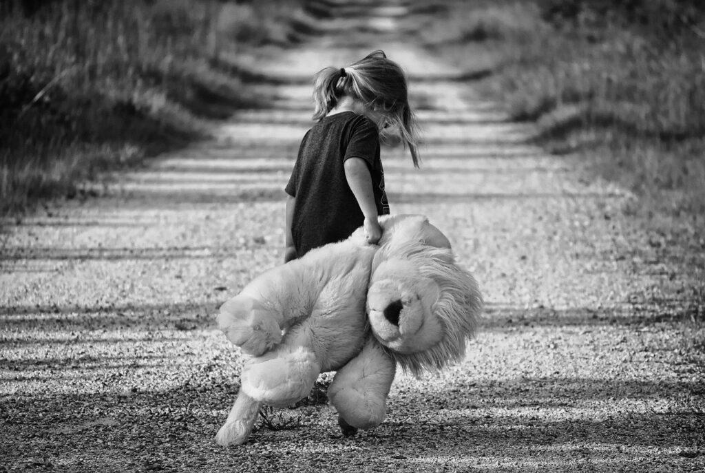 an unhappy girl dragging a teddy bear