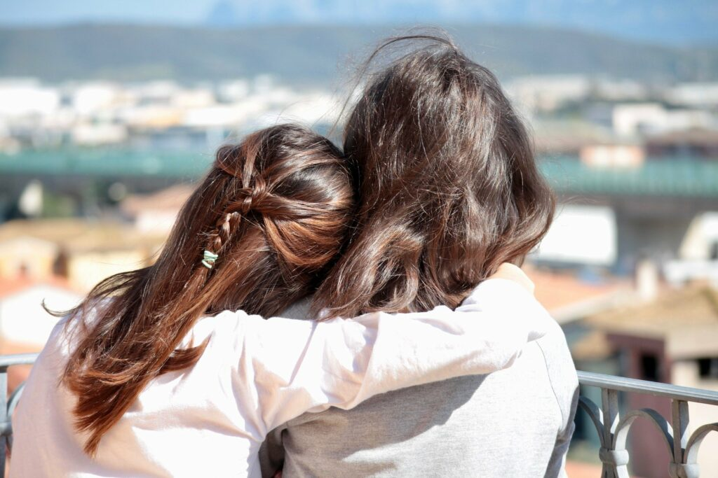 two woman side hugging