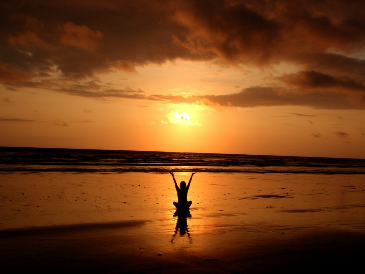man raising hands in front of sunset